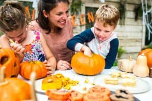 MOther with Children Carving Pumkins